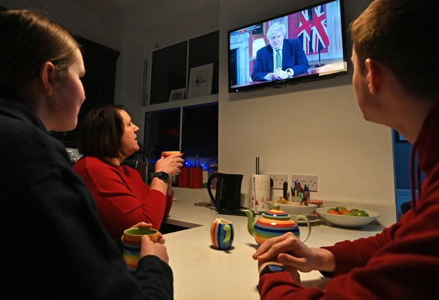 A family gather around the television to watch Britain's Prime Minister Boris Johnson give a televised message to the nation from 10 Downing Street in London (Photo by PAUL ELLIS/AFP via Getty Images)