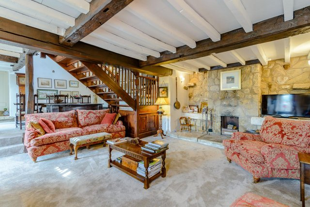 The lower level lounge has generous proportions and windows overlooking the courtyard and farmland beyond. A stone chimney breast is home to an inset open fire with a deep stone hearth.