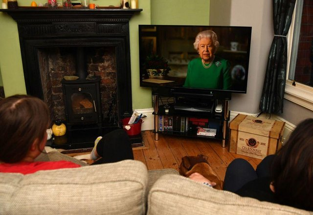 A family watching Britain's Queen Elizabeth II deliver a special address to the UK and Commonwealth recorded at Windsor Castle in relation to the coronavirus outbreak (Photo: PAUL ELLIS/AFP via Getty Images)