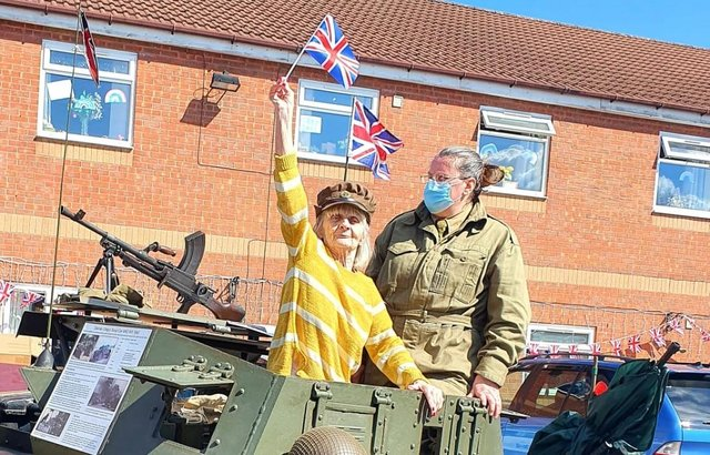 Jane Mosley, 77, waves the flag in the 'Dingo' Scout Car on its visit to Langdale Lodge Care Home in Chesterfield.