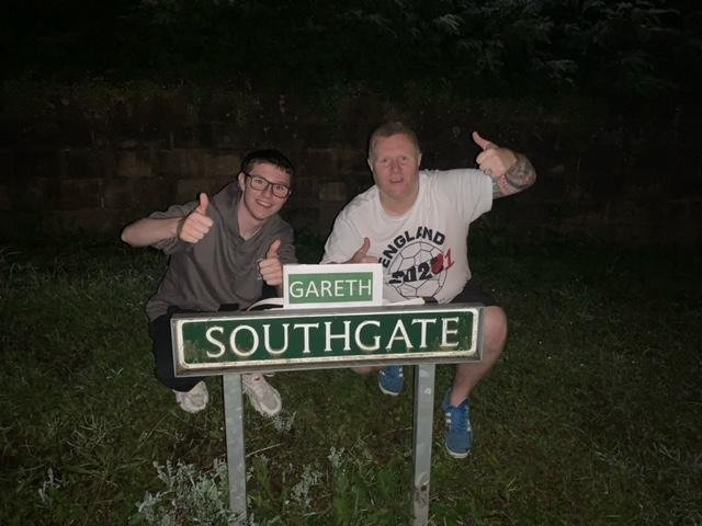 Chris Woolhouse and his stepson Jake Tindale with the amended 'Gareth Southgate' road sign in Eckington