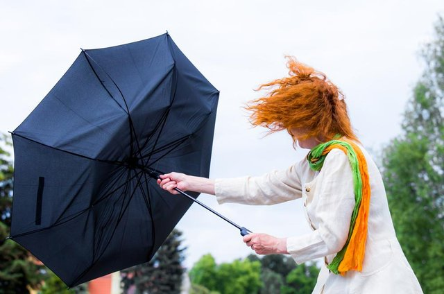 A woman tries to hold her umbrella in a strong wind.