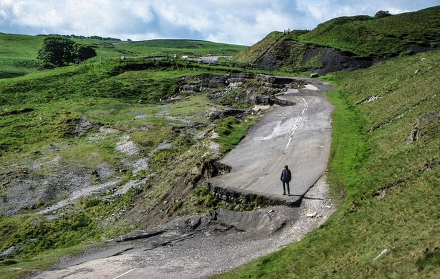 The old main road west of Castleton, closed since 1977, where walkers can now see the dramatic effects of the landslide that continues to move when saturated by rainfall every winter (photo by Tony Waltham Geophotos).