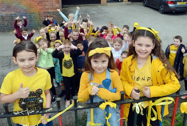 Tibshelf Infant and Nursery School children and parents tie ribbons on the school fence as part of the national day of reflection to mark one year since the first lockdown.