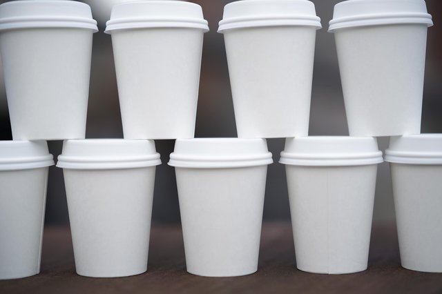 Disposable coffee cups are stacked on a table. Photo illustration by Christopher Furlong/Getty Images.