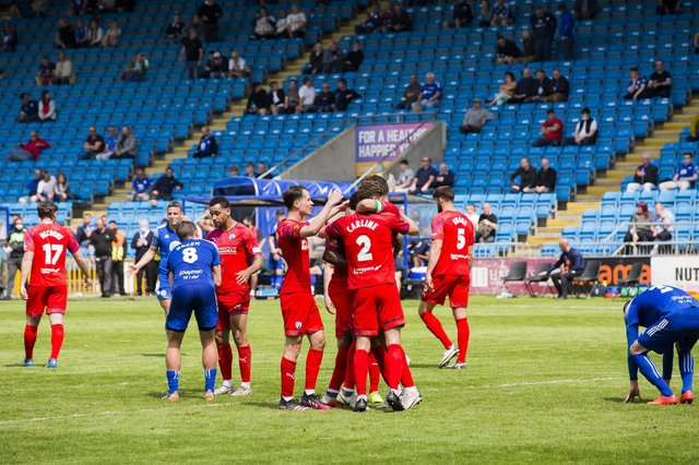 Spireites players celebrate at full-time after cementing their place in the play-offs.