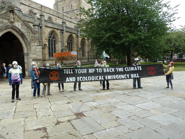 Extinction Rebellion campaigners outside Chesterfield's Crooked Spire church.