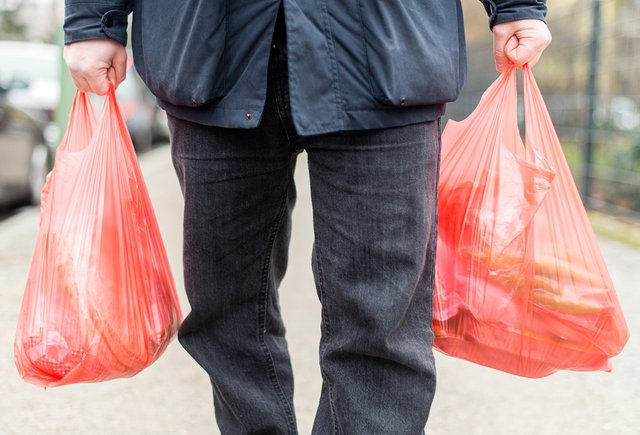 A man carrying his purchases in plastic bags. Credit: SEBASTIAN GOLLNOW/DPA/AFP via Getty Images.