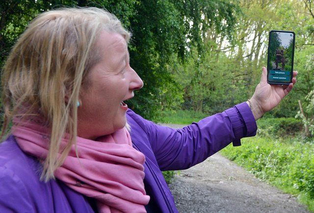 Coun Carolyn Renwick, cabinet member for economic growth at NE Derbyshire District Council, uses the new phone app to spot  a dinosaur in Ince Piece wood, Eckington.