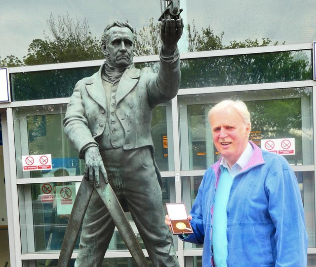 Dr Peter Broughton with his George Stephenson Medal by the statue outside Chesterfield railway station.