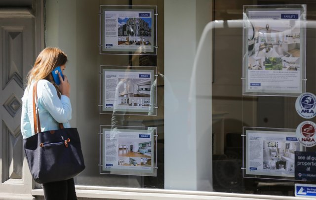 A woman looks at adverts in the window of an estate agent. Picture: DANIEL LEAL-OLIVAS/AFP via Getty Images.