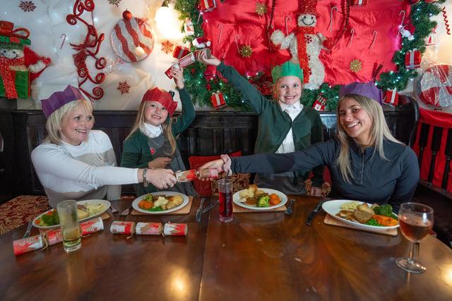 Joanne Stone, 50, Ivy Dakin 5 and Mia Dakin 7, Sarah Dakin 25, of Glossop, pull crackers.
