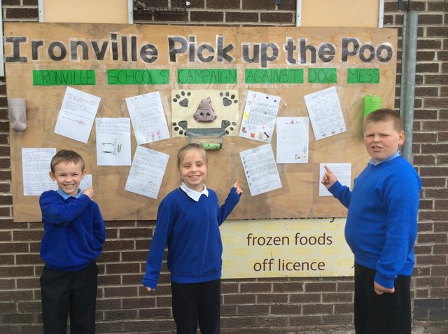 Pupils from Ironville and Codnor Park Primary School with their letters to dog owners on the community board outside the Post Office