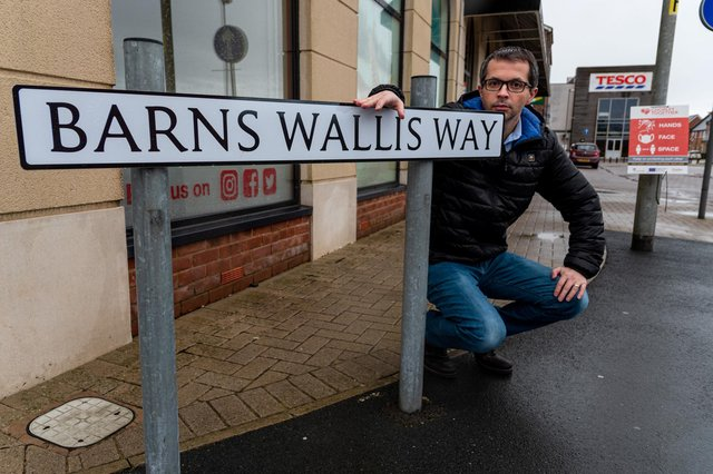 County Cllr Aidy Riggott with the Barnes Wallis Way street sign that has been spelt incorrectly