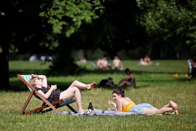 People sit on the grass in the sunshine. Photo by TOLGA AKMEN/AFP via Getty Images.